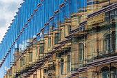 old building facade reflection in modern building glass facade - old building facade, new building exterior