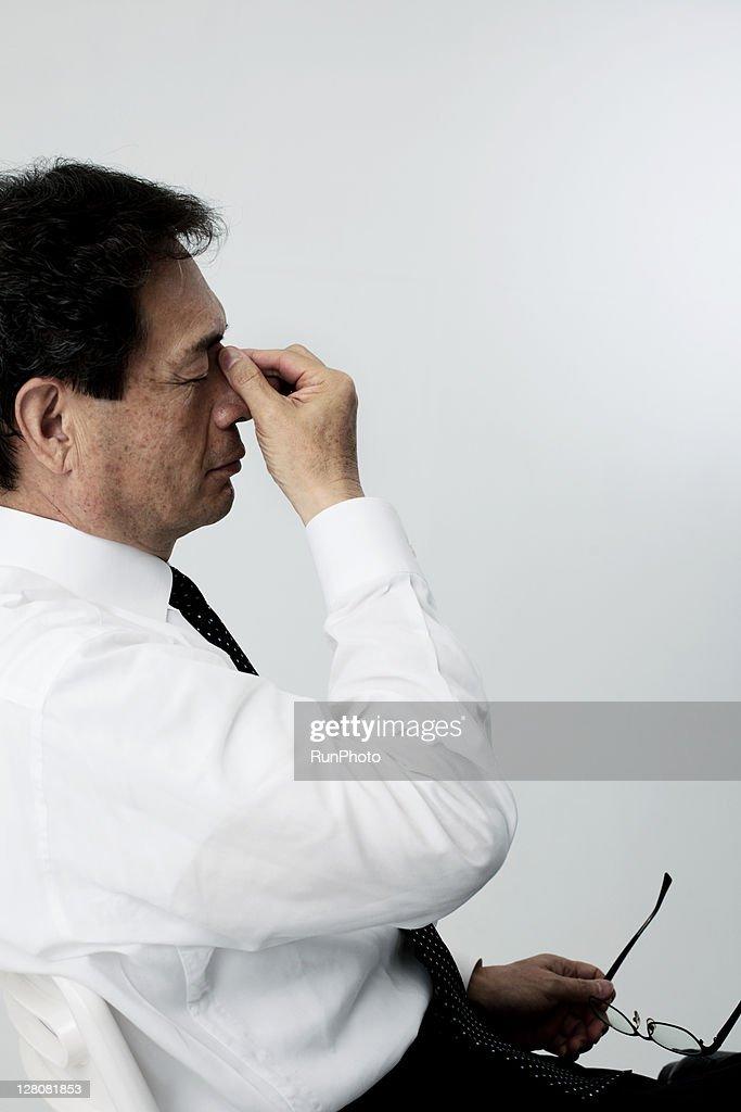 old businessman holding bridge of nose