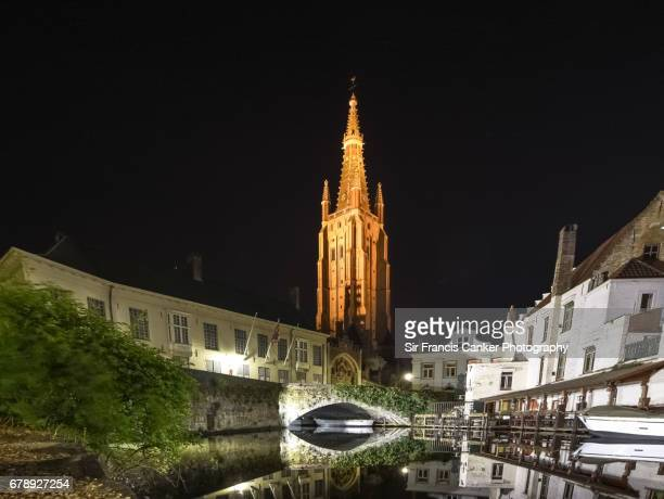 Old canal in Bruges with medieval bridge and majestic Church of our Lady brick-built bell tower on background in Flanders, Belgium