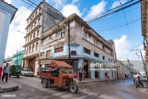 Old changed red tricycle or 'motoneta' used for transporting passenger inside the city Wide angle take of Cuban transportation and lifestyle