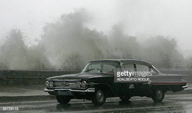 A old Chevrolet Impala passes by the Havana's Malecon splashed by waves while the Hurricane Rita starts barrelling Cuba 20 September 2005 Rita...