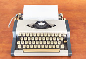 old classic vintage typewriter with sheet on wooden desk