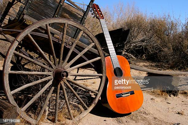 Old Classical Guitar in Western Scene with Wagon Wheel