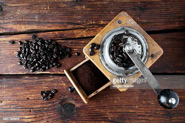 Old coffee grinder with coffee beans on a wooden surface