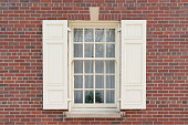 Old colonial window with shutters on historic brick building