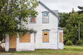 """an old white condemned two-story house with windows boarded up and a sign saying """"no trespassing"""" with a big green tree in front."""