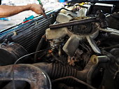 Old cooling fan motor of car is being removed in garage. Auto repair service.
