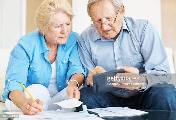 Old couple calculating their monthly finances at home