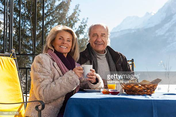 Old couple having breakfast at the hotels terrace