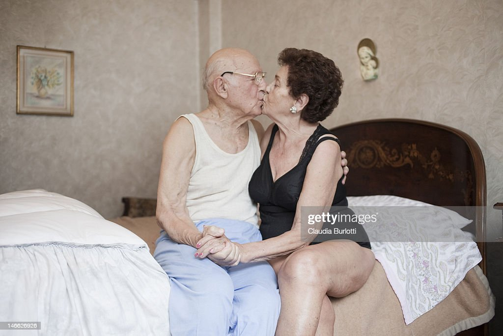 Old couple kissing holding hands : Stock Photo