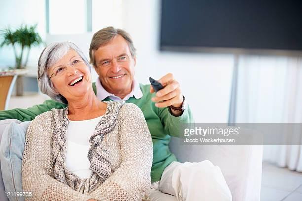 Altes Paar sitzt auf dem sofa beim Fernsehen