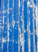 Closeup of old cracked paint texture on the side of a beach hut, Essex UK.