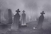 Old creepy haunted cemetery on misty night.