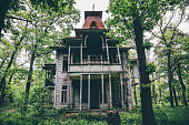Old creepy wooden abandoned haunted mansion house building among green forest
