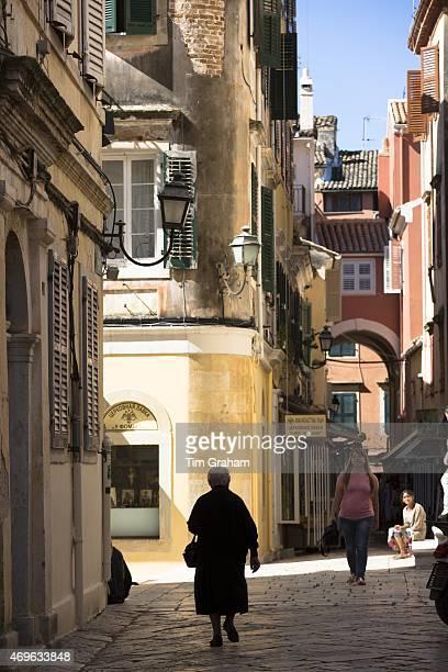 Old Cypriot woman in street scene by Church of Saint Spyridon in Kerkyra Corfu Town Greece