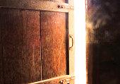 Old dark room with shining closed door.