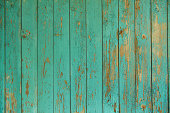 Close-up picture of turquoise wood wall.The wall is old and devastated with some paint chips here and there. The green paint is peeling off and tree appears under the green surface.