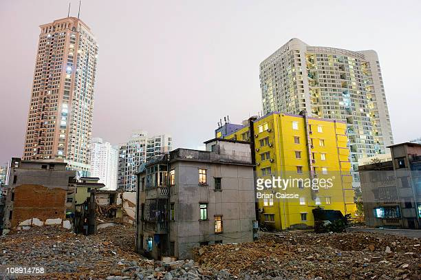 Old dilapidated buildings and rubble with modern buildings in background, Shenzhen, China