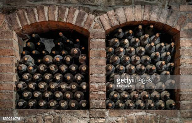 Old dusty wine bottles stored in two niches for aging in cellar