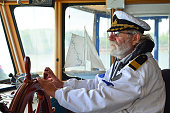Ship navigation, experienced captain, old sea dog with grey hair and beard on his working place, ship navigation cabin