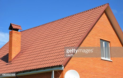 Old faded red metal roof tile and chimney. Bad roofing. : Stock Photo