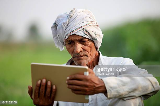 Old farmer holding digital tablet