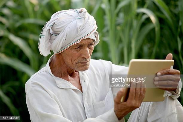 Old farmer holding I Pad