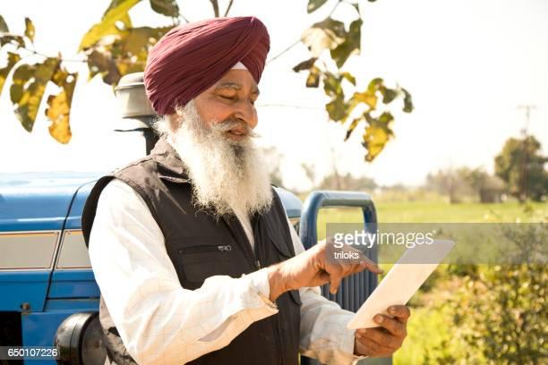 Old farmer using digital tablet
