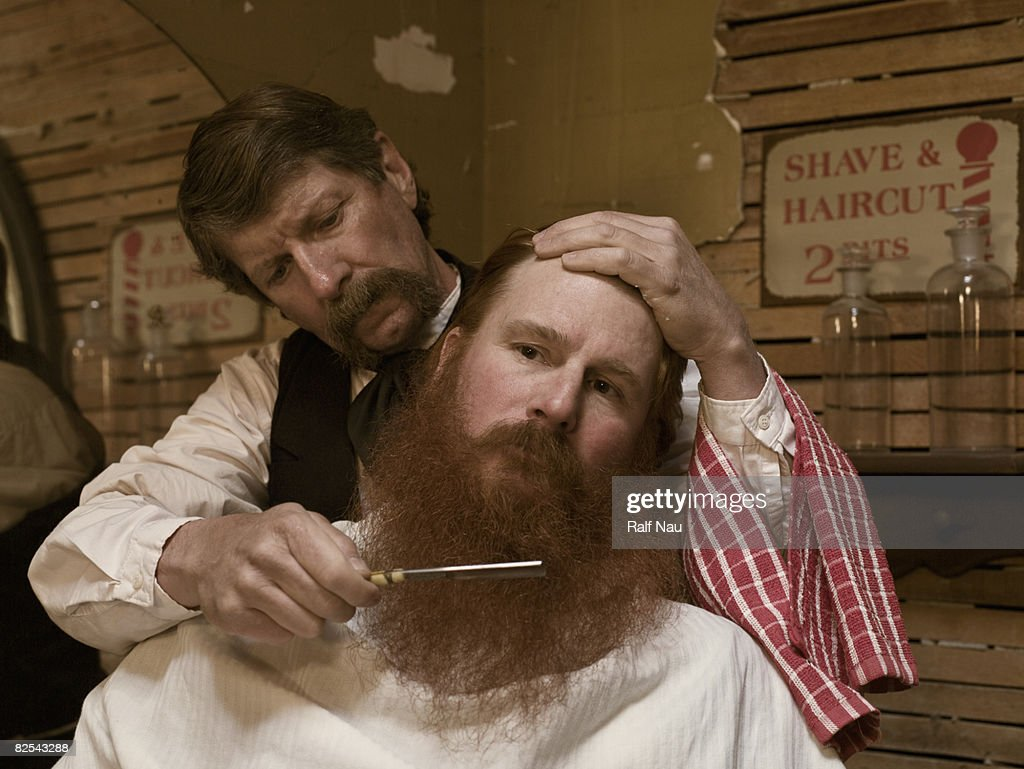 Old fashioned barber giving man a shave : Stock Photo