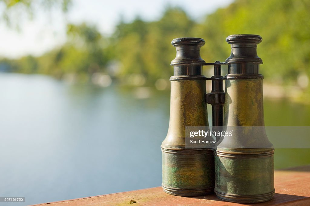 Old fashioned binoculars on a table beside a lake : Stock Photo