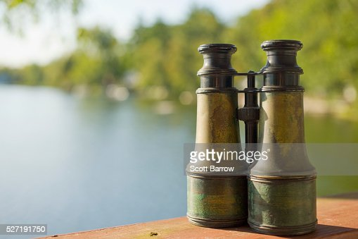 Old fashioned binoculars on a table beside a lake : Bildbanksbilder