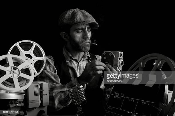Old Fashioned Cinema Director Posing With Cinema Equipments And Smoking