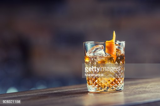 Old fashioned classic cocktail drink in crystal glass on bar counter : Stock Photo