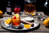 The Old Fashioned is most commonly made by muddling sugar cubes with bitters, a cherry and an orange wedge or peel. Usually a splash of water or soda water is added along with ice, bourbon (or rye) an