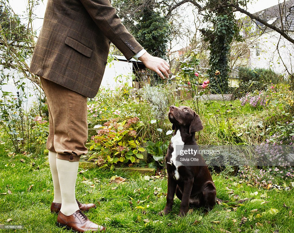 old fashioned dressed man feeding his dog : Stock Photo