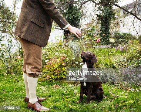 old fashioned dressed man feeding his dog : Stock Photo
