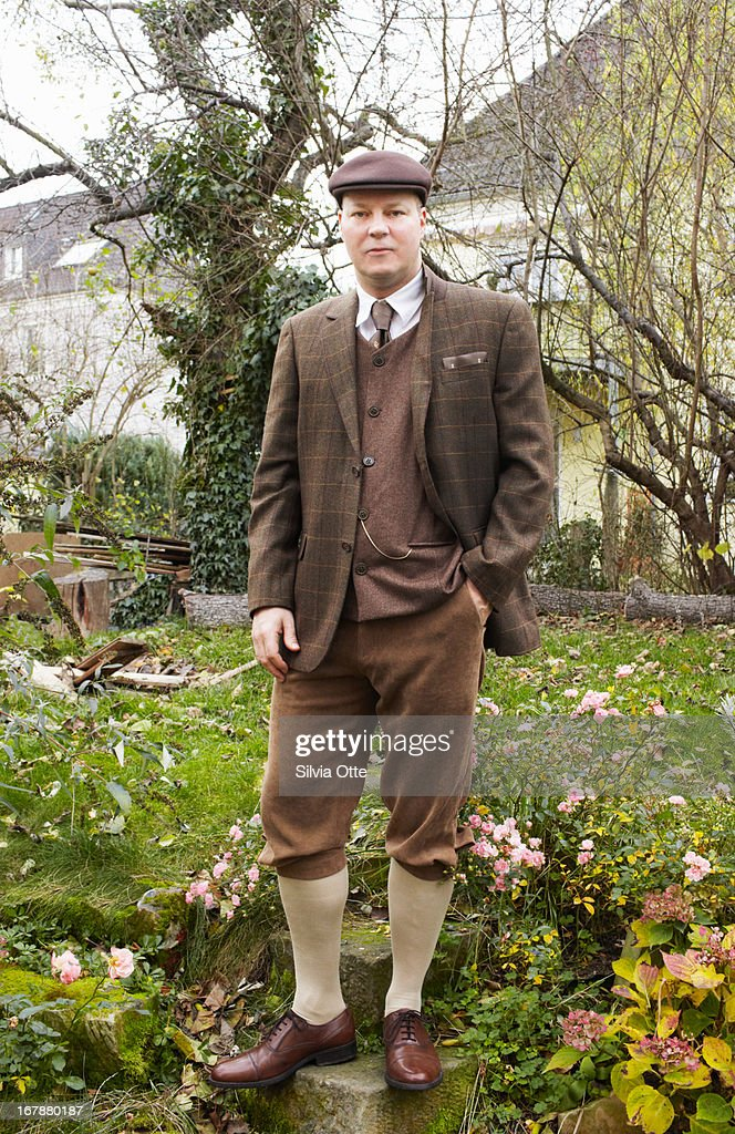 Old fashioned dressed man standing in garden : Stock Photo