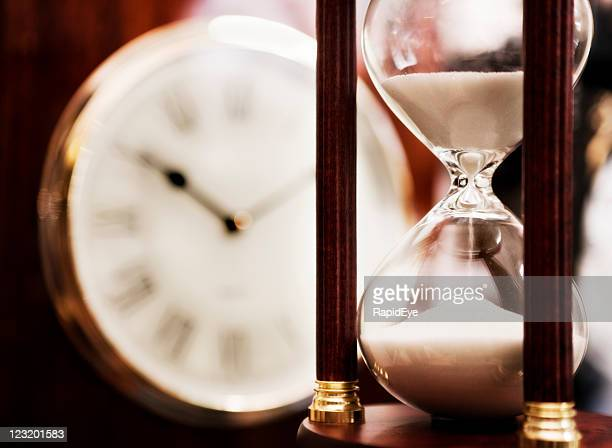 Old fashioned hourglass with clock dial in background