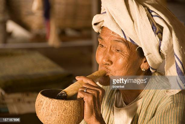 Old female smoking a hand-made cigar