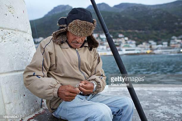 Old fisherman preparing bait