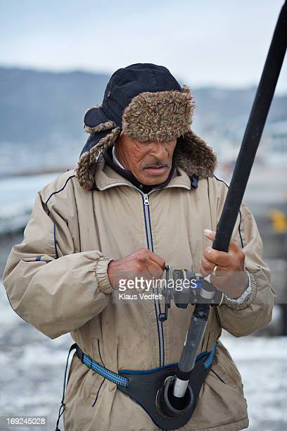 Old fisherman using wheel on fishing rod