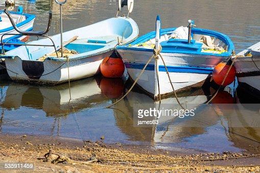 old embarcaciones pesqueras vinculados con la costa del mar calmo reflejo : Foto de stock