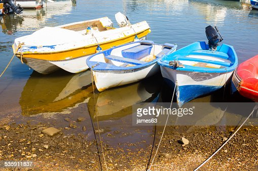 old fishing boats tied the shore with calm sea reflection : Stock Photo
