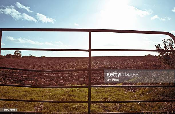 Old gate opening up to a tilled field