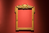old golden empty frame against red silk wallpaper
