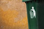 old green bins beside grunge yellow walls. please litter into bins symbol.