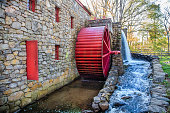 working water mill with a red wheel. Old stone grist mill in Sudbury, MA