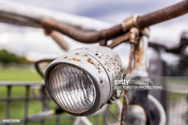 old, gritty, rotten, rusty, antique bicycle - headlight and handlebar in foreground