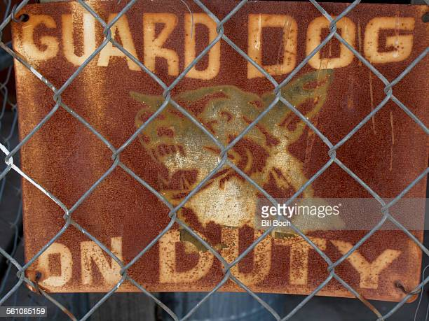 Old guard dog sign behind chain-link fence