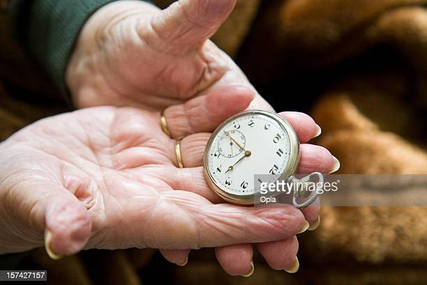 Old hands holding a silver pocket watch